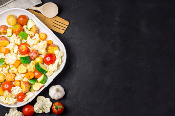 Various vegetables - tomatoes, cauliflower, zucchini, potato on dark background. Top view, copy space.