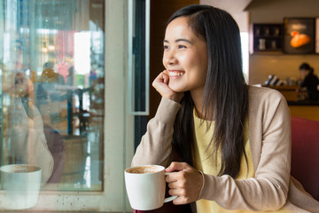 Asian woman sitting next to glass window inside coffee shop with cup of hot coffee in left hand