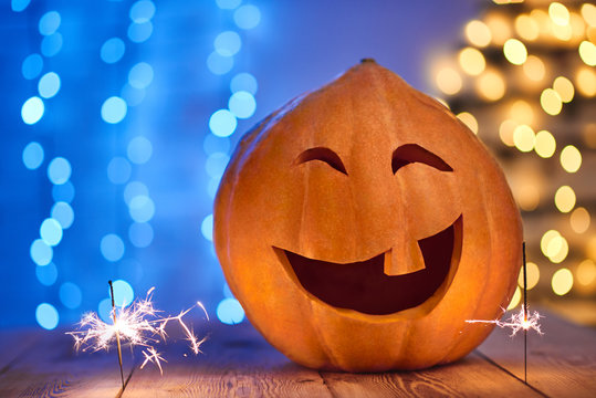 Close up of scary and funny big pumpkin with smile and one tooth, laughing and having fun. Decoration for Halloween against blue wall with lights. Prepare for celebration autumn holiday Halloween day.