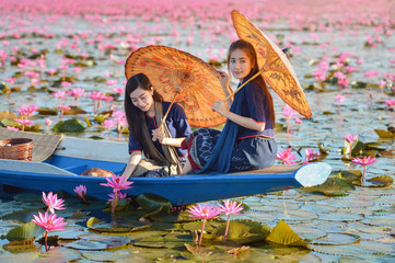 Laos woman in flower lotus lake, Woman wearing traditional Thai people , Red Lotus Sea UdonThani Thailand