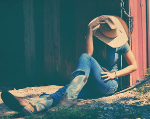 Cowgirl showing western fashion while sitting, wearing cowboy hat and boots.