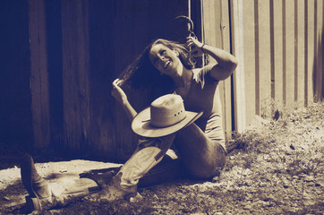 Cowgirl taking a break from farm work in the barn, rustic background ranch image.