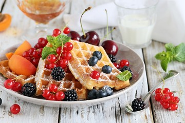 Waffles with fresh seasonal berries and honey. Dessert with berries and apricots. Selective focus