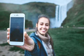smiling woman in warm clothes making selfie on a Skogafoss waterfall background, Iceland. Focus on the phone