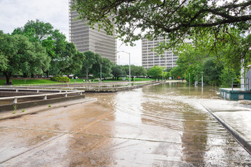 High and fast water rising in Bayou River from Montrose boulevard with near town Houston in background, cloud sky. Heavy rains from Tropical Hurricane storm caused many flood in greater Houston areas