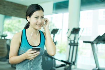 Asian Woman using Smartphone while Exercise at Gym. Woman do exercise alone with attractive Smiling. Woman with Exercise Concept