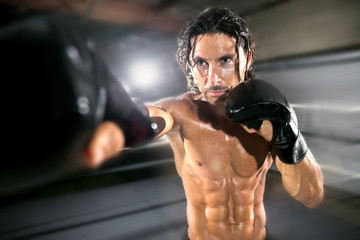 Conceptual sports virtual reality muscular fitness fighter with abs and ripped chest throwing a punch