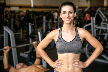 Commercial type fitness model with perfect smile, cheerful at the gym during exercise