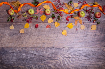 Autumn arrangement of leaves, apples and berries on a wooden background with free space for text. Top view, concept of the season