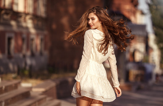 Beautiful young girl with long healthy hair, nice dress walking in the street. Lifestyle concept. Youth and happiness.