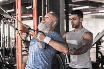 Mature male is having workout with trainer in modern gym