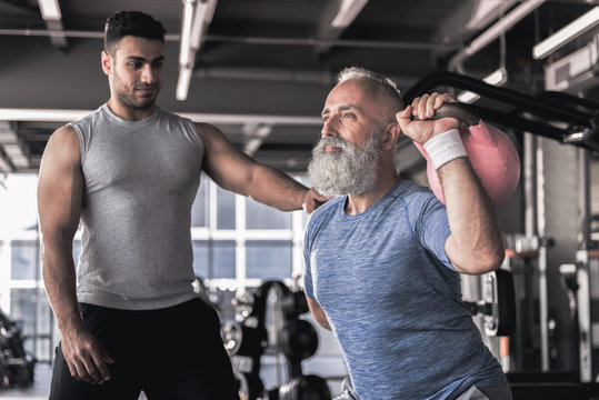 Senior male doing exercises with young instructor in modern gym