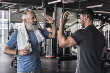 Photo sur Aluminium Fitness Cheerful males are talking to each other in modern gym