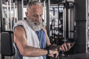 Positive old male is spending time in athletic center