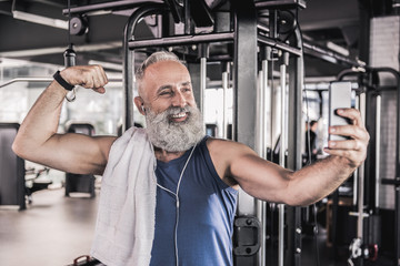Joyful senior male making picture of himself in modern gym