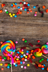 Colorful candies borders on wooden background with copy space