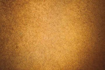 Old aged suede leather background. Coarse texture, gradient yellow brown beige, vivid colors. Vignette, toned.