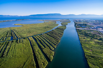View from the air at the place where the river flows into the sea in southern Croatia. River Neretva estuary.