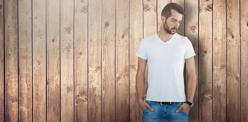 Composite image of thoughtful male model with hands in pockets