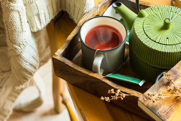 Mug with hot red fruit tea, green pot, book on tray, knitted sweater hanging over wooden chair, cozy atmosphere, autumn, fall