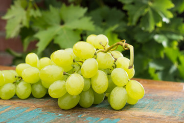 Healthy fruits White wine grapes on the wooden table in the vineyard, wine grapes, bunch of grapes ready to eat