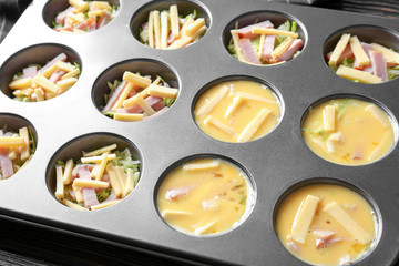 Whipped eggs, sliced cheese and ham in baking mold, closeup