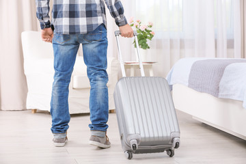 Young man with luggage in hotel room