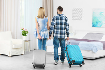 Young couple with luggage in hotel room