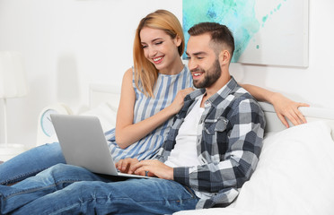 Young couple using laptop in hotel room