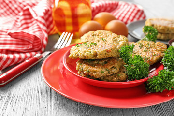 Broccoli pancakes served with fresh parsley on red plate