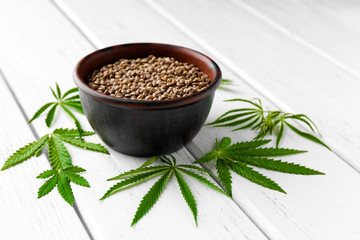 Bowl with hemp seeds on wooden background