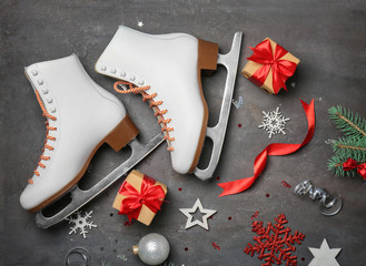 Figure skates with gifts on grey background