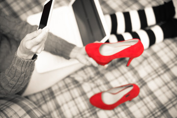 Top view closeup of red shoes and woman using laptop on the bed background. Closeup on busy communication lifestyle