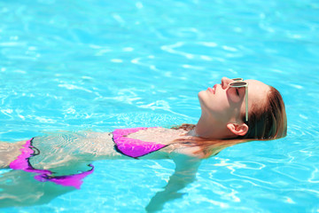 Beautiful young woman in swimming pool