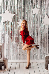 Young sexy lady standing on one leg in high heels and red dress.