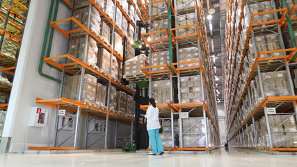 Large modern warehouse with forklifts. Warehouse worker taking package in the shelf in a large warehouse in a large warehouse. storehouse worker sealing cardboard boxes for shipping in storehouse.