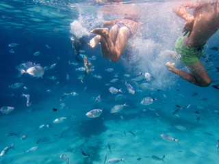 underwater photo with kids swimming along with fish