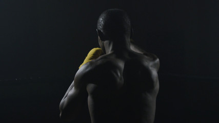 Rear view of muscular man boxing on black background. Afro american young male boxer practicing shadow boxing. Boxer in yellow Boxing gloves