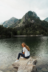 Woman sitting on stone at lake