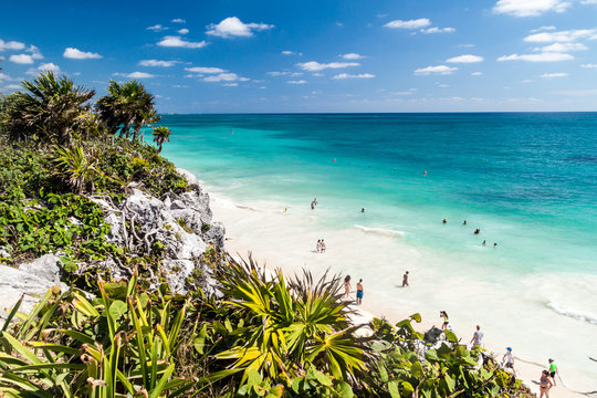 TULUM, MEXIO - FEB 29, 2016: Tourists at the beach under the ruins of the ancient Maya city Tulum, Mexico