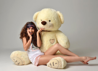 Young beautiful girl hugging big teddy bear soft toy happy smiling