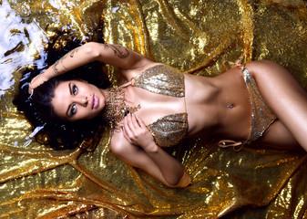 Young beautiful sexy woman lying in gold water drops in bikini and expensive jewelry