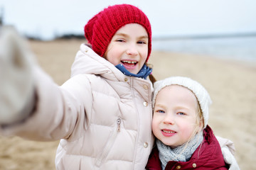 Two cute little sisters taking a picture of themselves at winter beach on cold winter day. Kids playing by the ocean.