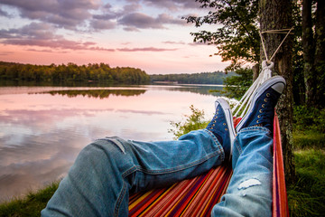 Summer camping by the lake. Young man wearing jeans and sneakers relaxing in the hammock at sunset.