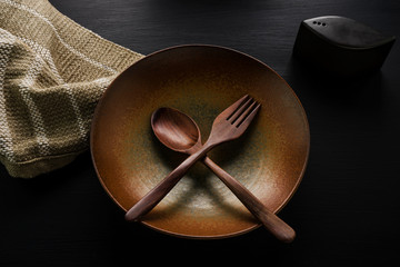 Ceramic dish(plate) and wooden spoon,wooden fork on table