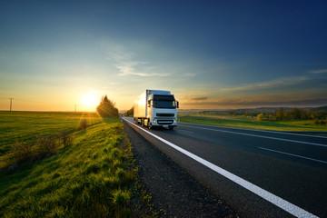 Fotobehang - White truck driving on the asphalt road in rural landscape at sunset