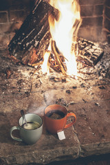 Hot cups of coffee and tea in a fireplace.