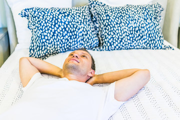 Young happy man laying down on bed closeup with pillows, comforter in bedroom of house, home or apartment