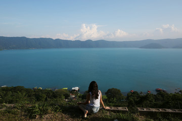 A woman poses for a picture with the Coatepeque Lake as background in the town of El Congo