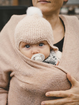Portrait of mother carrying baby girl in sweater